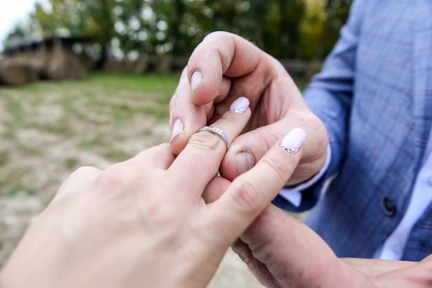 Mani del matrimonio con anelli. la sposa indossa l'anello.
