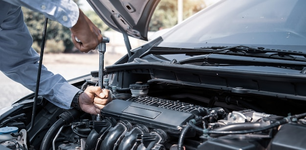 Mani del meccanico che usando chiave per riparare un motore di automobile.