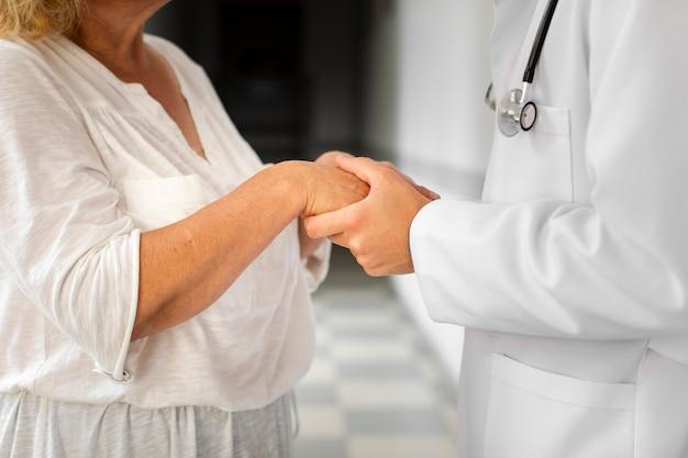 Mani del medico che tengono le mani della donna senior