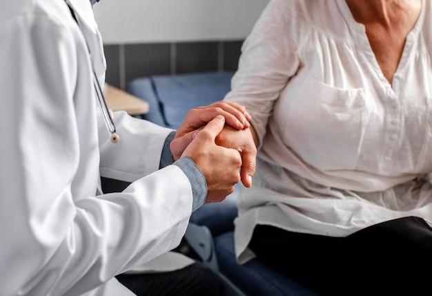 Mani del medico che tengono paziente femminile