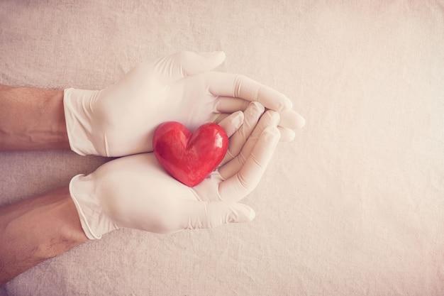 Mani del medico con i guanti che tengono cuore rosso, assicurazione sanitaria, concetto di donazione