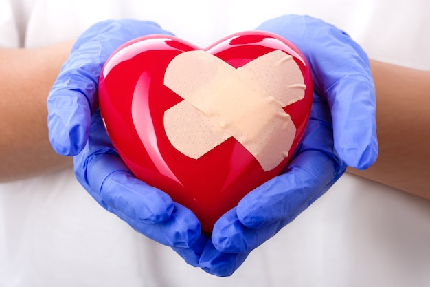 Mani del medico in guanti blu che tengono cuore intonacato