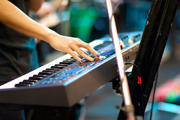 Mani del musicista che giocano tastiera di concerto con profondità di campo, messa a fuoco sulla mano destra