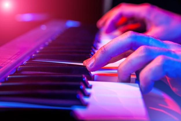 Mani del musicista che suonano la tastiera di concerto