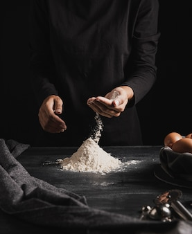 Mani del panettiere del colpo medio che mescolano farina