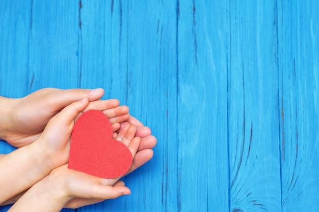 Mani del papà e del bambino che tengono cuore rosso.