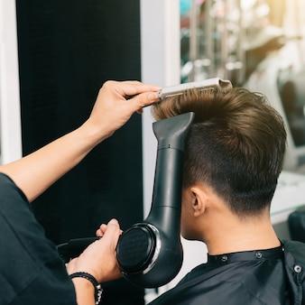 Mani del parrucchiere irriconoscibile che danno al cliente maschio soffiare con asciugacapelli e pettine