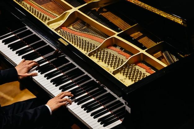 Mani del pianista classico che suonano il suo pianoforte durante un concerto.