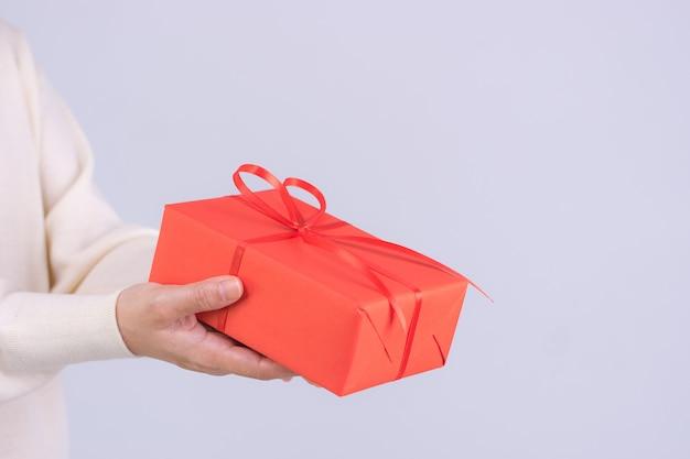Mani del primo piano che danno il contenitore di regalo. la donna consegna un pacchetto regalo rosso con nastro rosso. compleanno, santo stefano o concetto di natale.