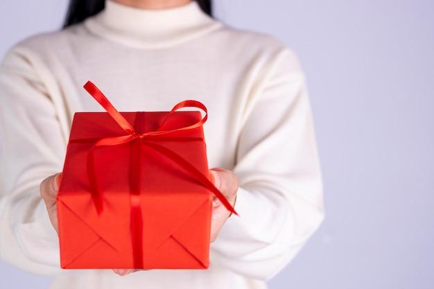 Mani del primo piano che danno il contenitore di regalo. la donna consegna un pacchetto regalo rosso con nastro rosso