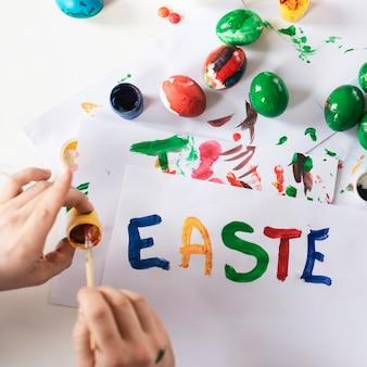 Mani del primo piano che dipingono le uova di pasqua tradizionali