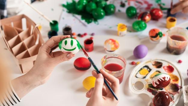 Mani del primo piano che dipingono uovo per pasqua