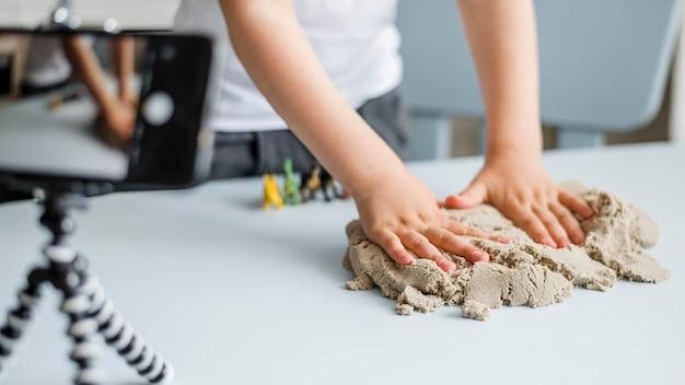 Mani del primo piano che giocano con la sabbia