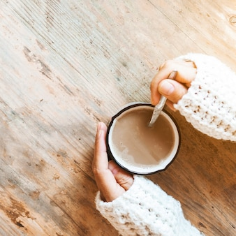 Mani del primo piano che mescolano caffè in tazza