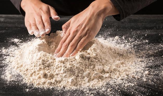 Mani del primo piano che premono farina
