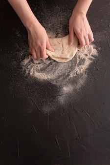 Mani del primo piano che producono pane