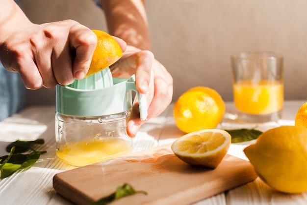 Mani del primo piano che schiacciano limone