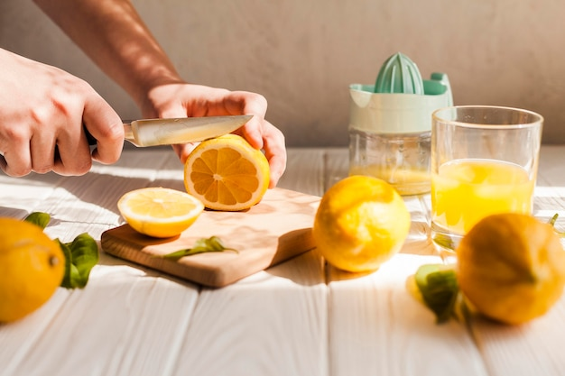 Mani del primo piano che tagliano limone con il coltello