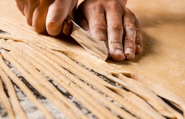 Mani del primo piano che tagliano pasta