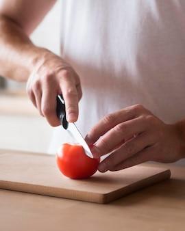 Mani del primo piano che tagliano pomodoro