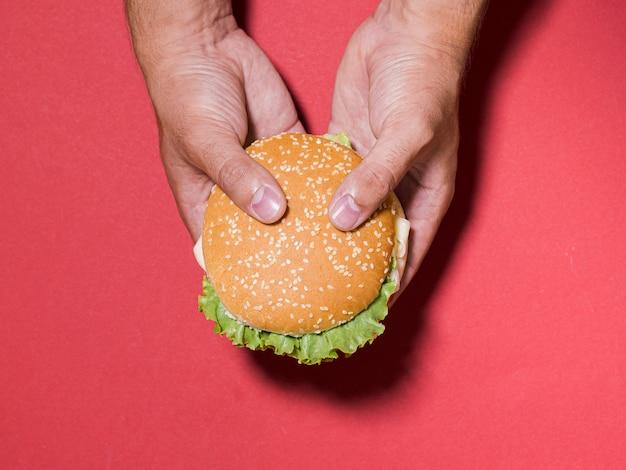 Mani del primo piano che tengono cheeseburger