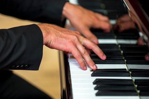 Mani del primo piano che tengono gli accordi sul pianoforte classico