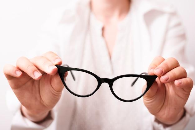 Mani del primo piano che tengono gli occhiali