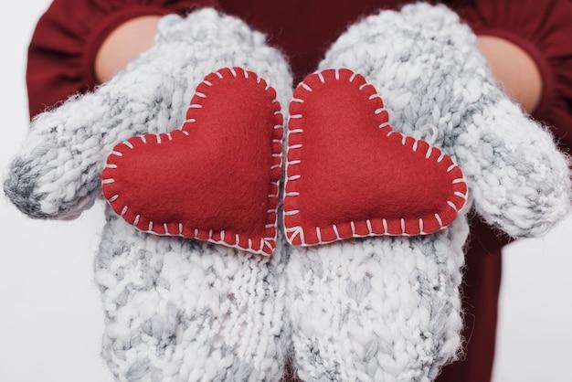 Mani del primo piano che tengono i cuori di amore