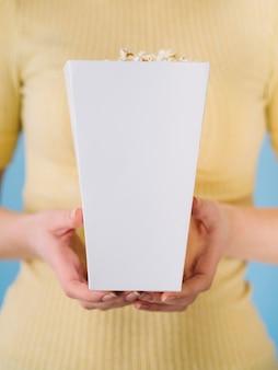 Mani del primo piano che tengono il contenitore di popcorn