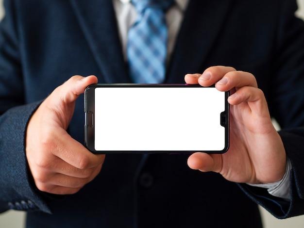 Mani del primo piano che tengono il modello del telefono