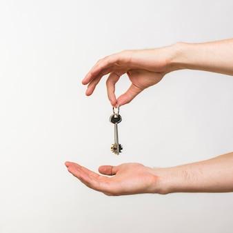 Mani del primo piano che tengono le chiavi