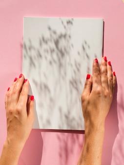 Mani del primo piano che tengono libro bianco con le ombre