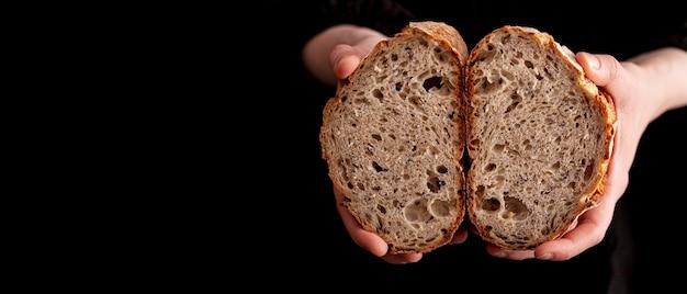 Mani del primo piano che tengono pane saporito