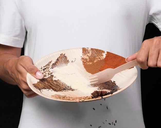 Mani del primo piano che tengono piatto