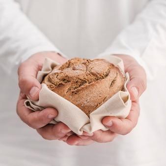 Mani del primo piano che tengono piccolo pane