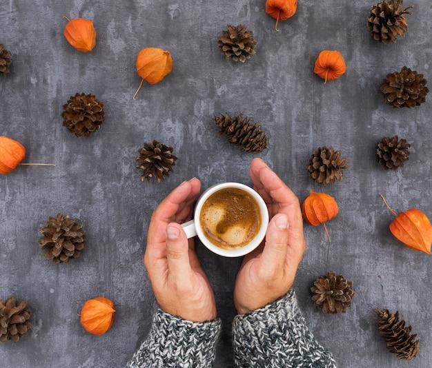 Mani del primo piano che tengono tazza con caffè