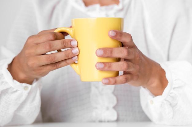 Mani del primo piano che tengono tazza gialla