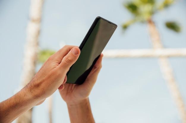 Mani del primo piano che tengono telefono nero