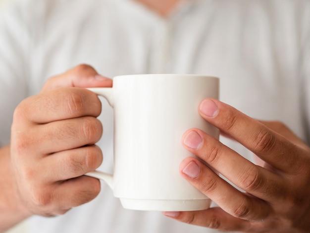 Mani del primo piano che tengono un modello della tazza
