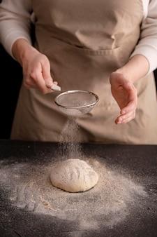 Mani del primo piano che versano farina su pane