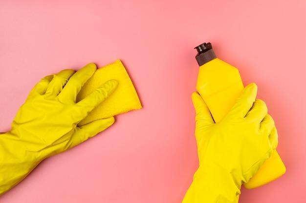 Mani del primo piano con i guanti che puliscono