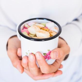 Mani del primo piano con la tazza di bevande e marshmallow