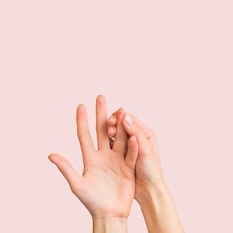 Mani del primo piano con sfondo rosa