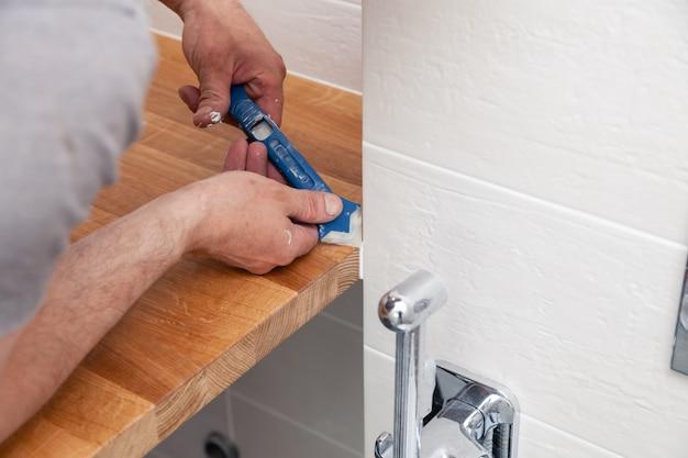 Mani del primo piano dell'operaio idraulico professionista che applica sigillante bianco, composto unito, mastice al giunto del piano d'appoggio di legno, parete piastrellata beige con piastrella rettangolare usando la ruspa spianatrice blu
