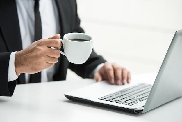 Mani del primo piano dell'uomo sul lavoro con il computer portatile e il caffè.