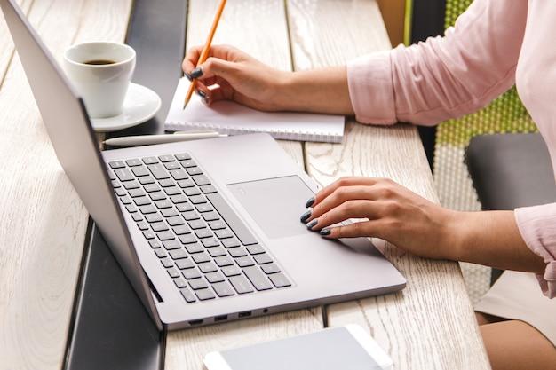 Mani del primo piano della donna di affari in camicia di rosa pastello che lavora al computer portatile e che fa gli avvisi in suo taccuino sulla tavola di legno con una tazza di caffè