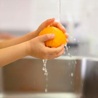 Mani del primo piano di un bambino che lava un limone