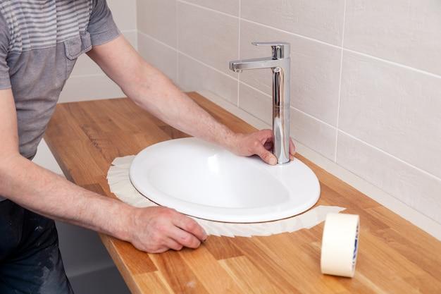 Mani del primo piano di un lavoratore idraulico professionista installa un lavandino in ceramica ovale bianco su un tavolo di legno in bagno con piastrelle beige, incolla sopra il lavandino con nastro adesivo per l'applicazione di sigillante