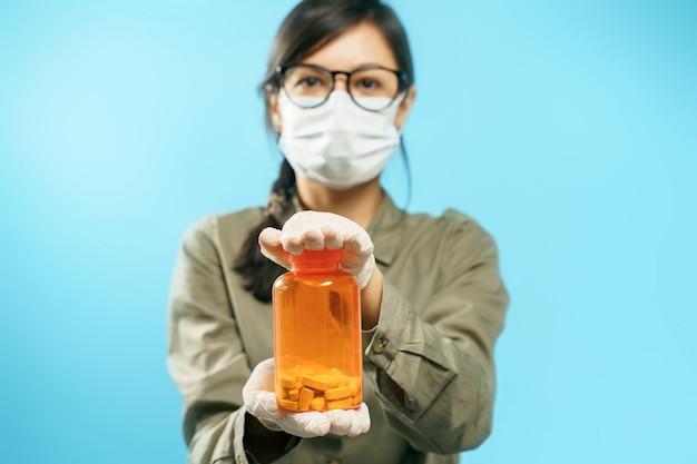 Mani del primo piano di una giovane donna in una mascherina protettiva medica e guanti che tengono una latta arancione con le pillole su una priorità bassa blu. prevenzione o trattamento di virus e influenza