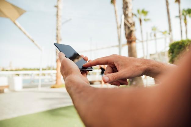 Mani del primo piano tramite smartphone